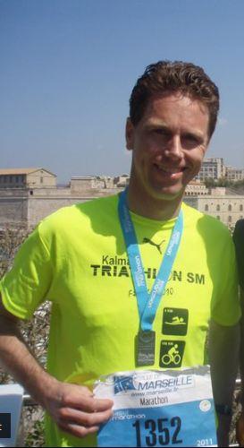 Fritte poserar stolt med medalj efter genomfört marathon